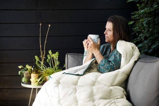 Kvinde drikker kaffe omsluttet af en kapokdyne