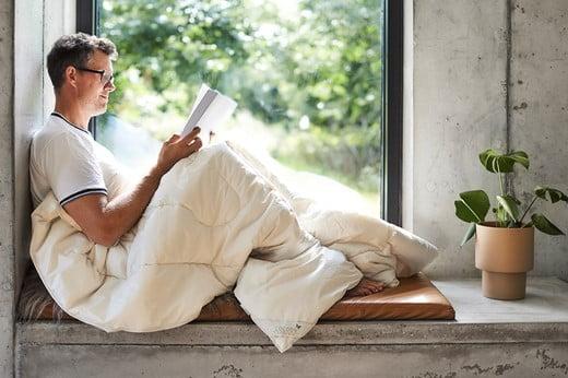 Mand i vindue med merinoulddyne