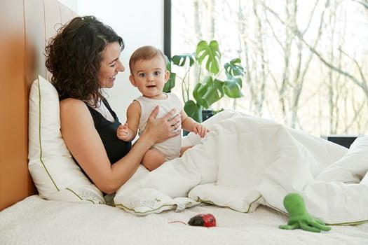 Mor og barn sidder i sengen med en dyne og pude fra Amazing Maize