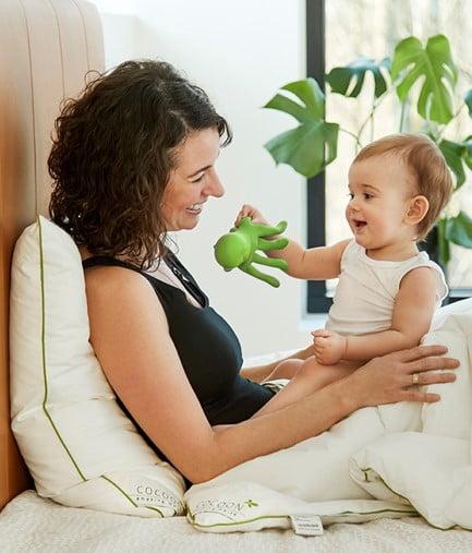 Mor og barn som sidder i seng med Amazing Maize dyne og pude